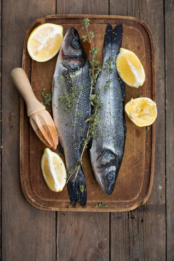 Fresh raw seabass and ingredients for cooking. Two fish seabass with lemon, spices and herbs on wooden table, top view with copy s stock image