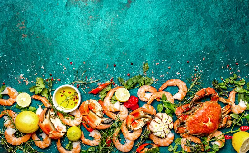 Fresh raw seafood - shrimps and crabs with herbs and spices on turquoise background. Copy space.  stock photography
