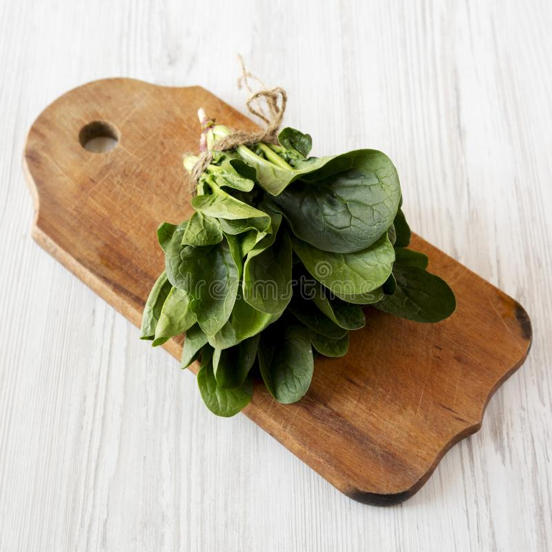 Fresh raw spinach on a rustic wooden board on a white wooden surface, low angle view. Closeup.  stock photos