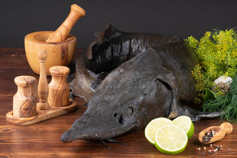 Fresh raw sturgeon fish on the table with lemon pepper garlic. clouse up stock photo