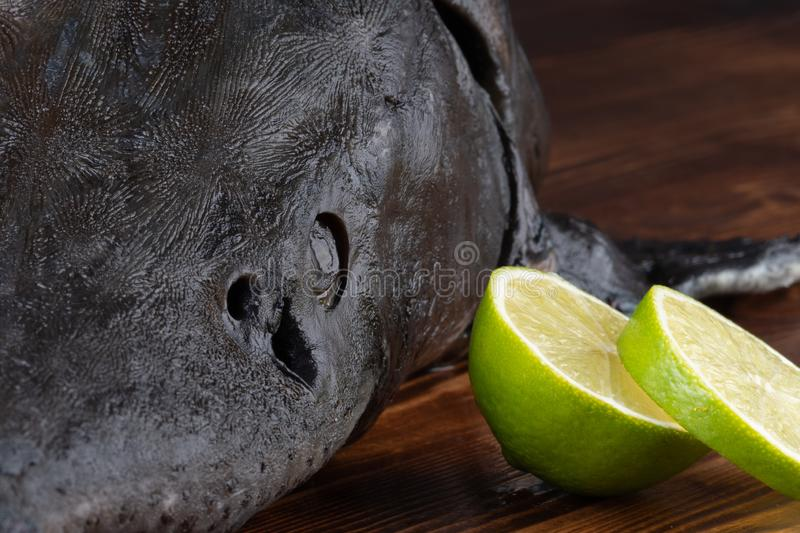 Fresh raw sturgeon fish on the table with lemon pepper garlic. clouse up.  stock photography