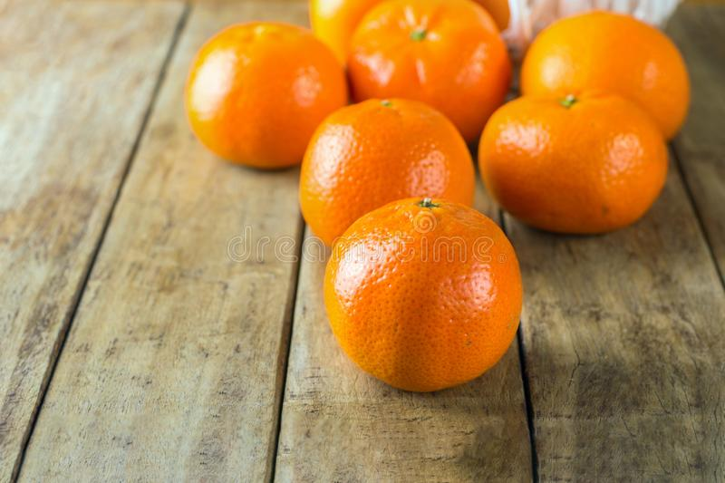 Fresh raw tangerines spilled from wicker basket on plank wood rustic table. Healthy food plant based diet citrus fruits vitamins. Concept. Minimalist poster royalty free stock images