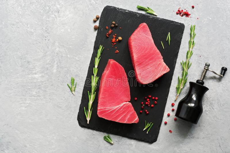 Fresh raw tuna steak with spices on a black slate plate. gray background. Top view, flat lay.  stock image
