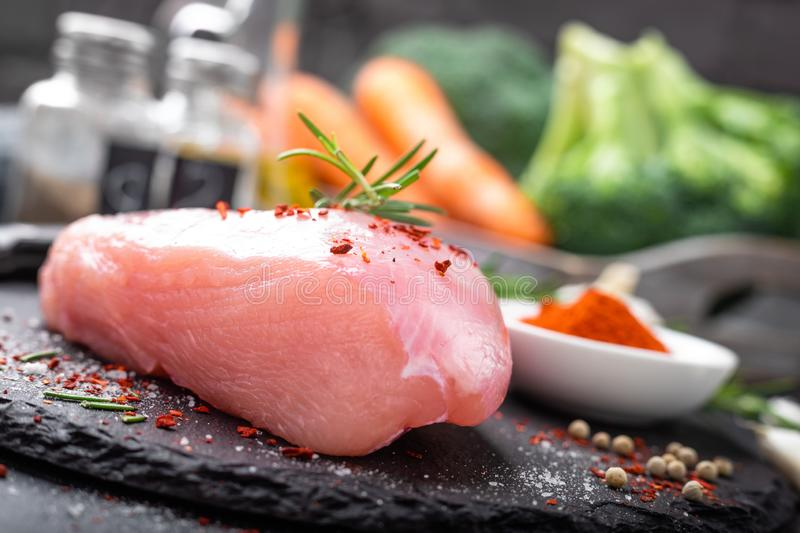 Fresh raw turkey meat fillet with ingredients for cooking on board royalty free stock photography