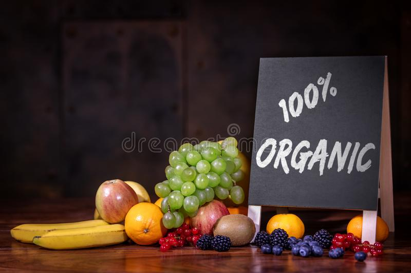 Fresh raw variety of fruits on wooden table, Slate or board with text 100% organic stock photo