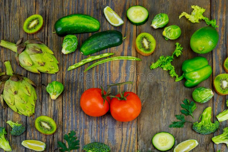 Fresh raw vegetable ingredients for healthy cooking or salad making with rustic wood board in center, top view, copy space. royalty free stock photography