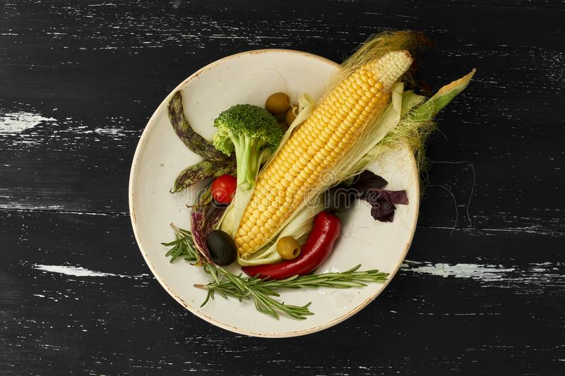 Fresh raw vegetables on round plate. Fresh raw vegetables on round ceramic plate standing on blue aged wooden surface. Top view stock images