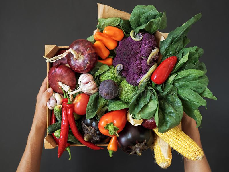 Fresh vegetables in a wooden box on a black background. Hands holding a box. Harvesting. Top view. Fresh, raw vegetables in a wooden box on a black background stock photo