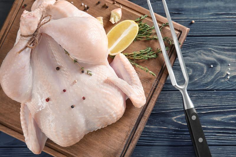 Fresh raw whole chicken with spices and lemon stock images