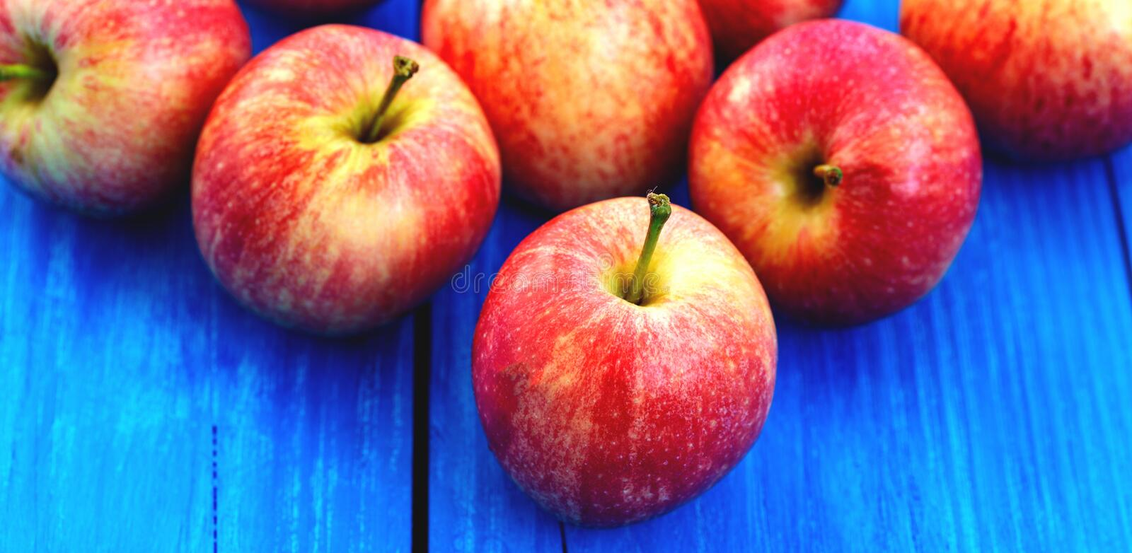 Fresh red apples on the blue wood background.  stock photography