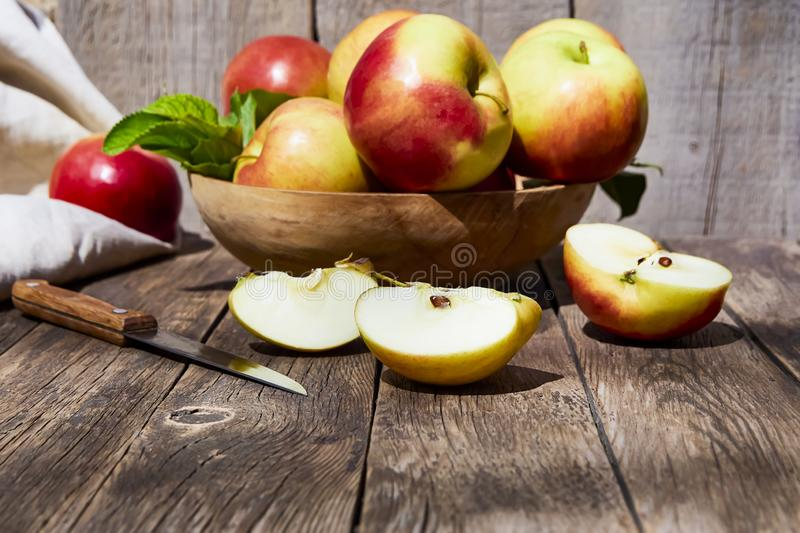 Fresh red apples with green leaves on a wooden old table. On a wooden background. royalty free stock photo