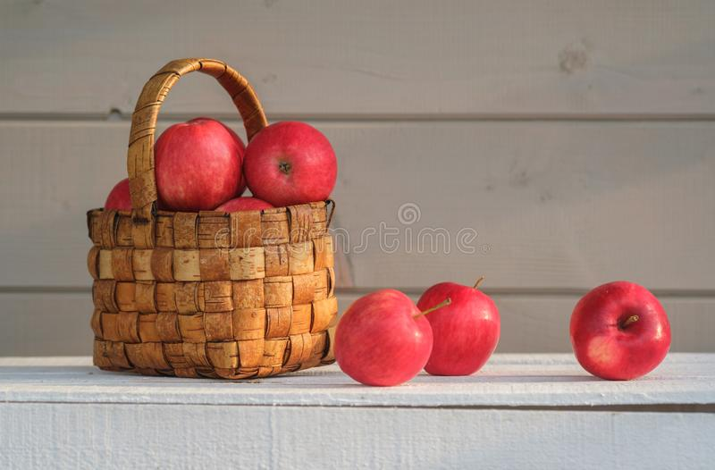 Fresh red apples in vintage wicker basket. On white box on grey wall background stock images