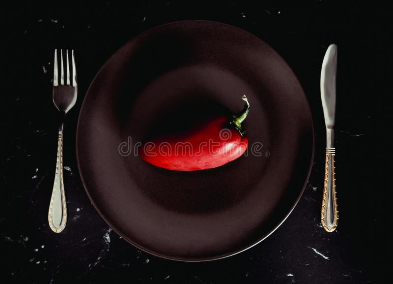Fresh Red bell pepper paprika on a plate. Diet. Dark background stock photo