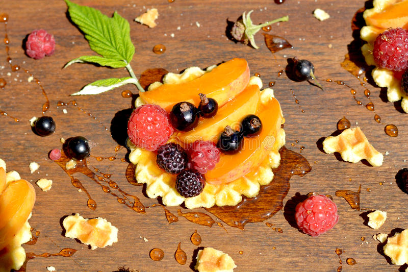 Fresh red, black raspberry and currant, peach, honey drop on waffle on wooden background close up. Fresh red, black raspberry and currant, peach, honey drop on royalty free stock photography
