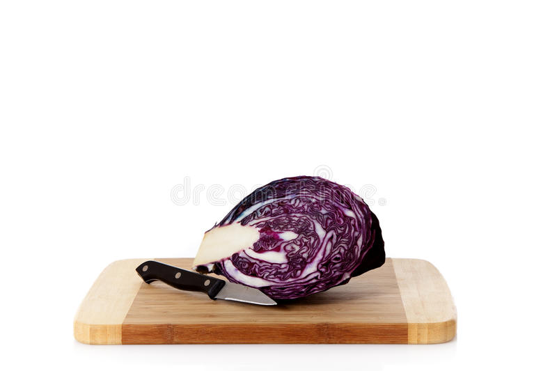 Fresh red cabbage, wooden chopping board. Fresh red cabbage and a knife on a wooden chopping board. Studio shot. White background. Copy space royalty free stock photo