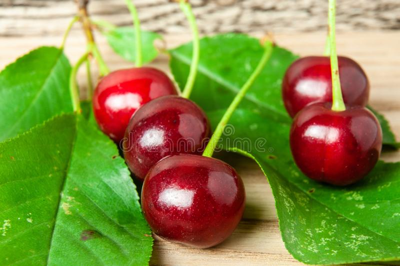 Fresh red cherries with green leaves on wooden table stock photo