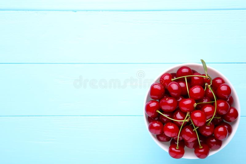 Fresh red cherry fruit in plate on blue wooden table stock photos