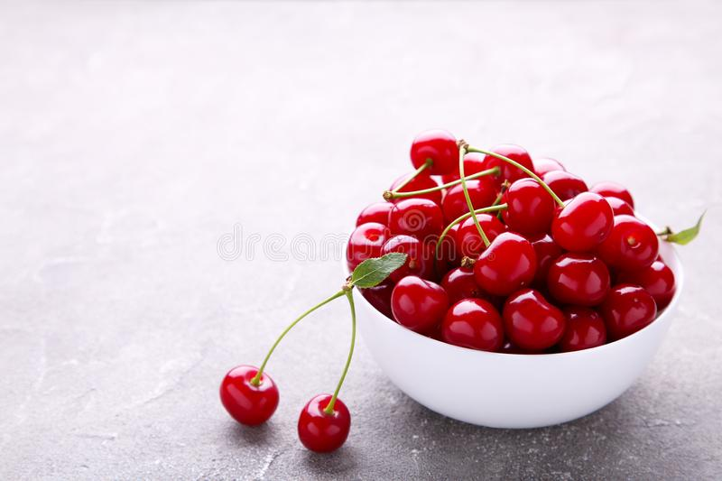 Fresh red cherry fruit in plate on grey concrete background stock photography