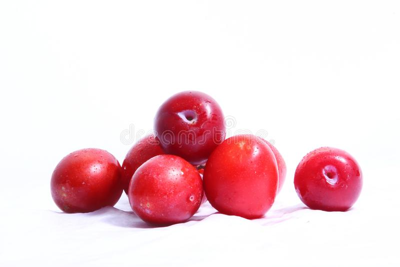 Red cherry plum. Fresh red cherry plum on white background. water sprayed over fruits stock images