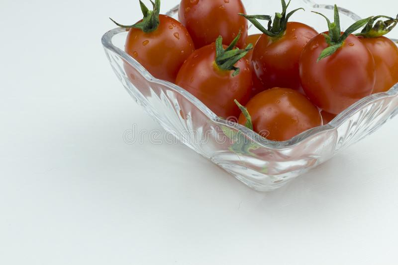 Fresh red cherry tomatoes with water drops in a glass bowl on a white background. Close up view, isolated tomatoes stock photos