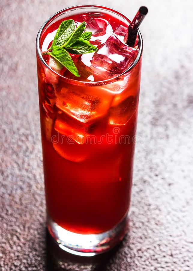 Fresh red cocktail with ice cubes and mint leaves. Red summer berries or pomegranate. Tasty drink stock photography