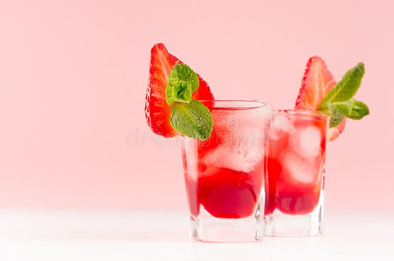 Fresh red fruit cocktail with ice cubes, strawberry slice, green mint in elegant misted shot glasses on soft light pink color. stock photography