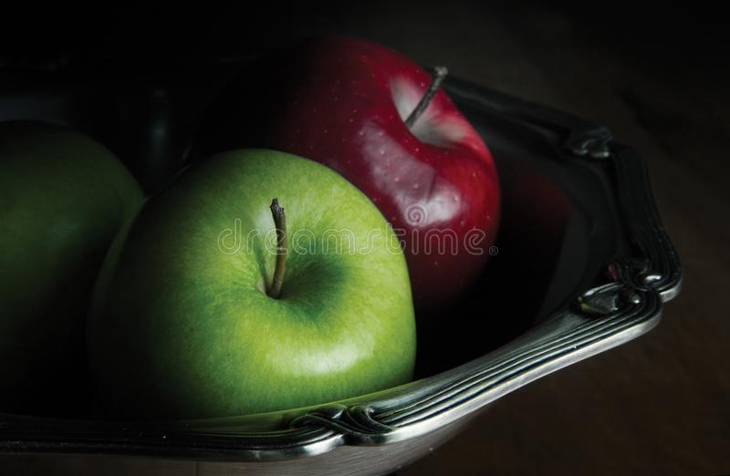 Fresh Red and Green Apple in the silver bowl on rustic wood table Background stock image