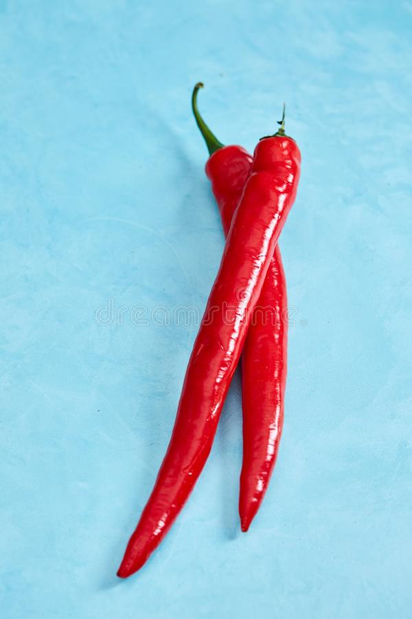Fresh red hot pepper on a blue background, top view, close-up royalty free stock photo