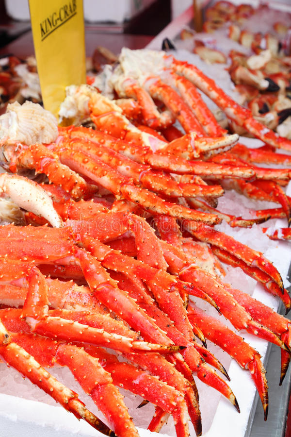 Fresh red king-crab legs in ice at seafood market. Cabs high content protein and low calorie royalty free stock images