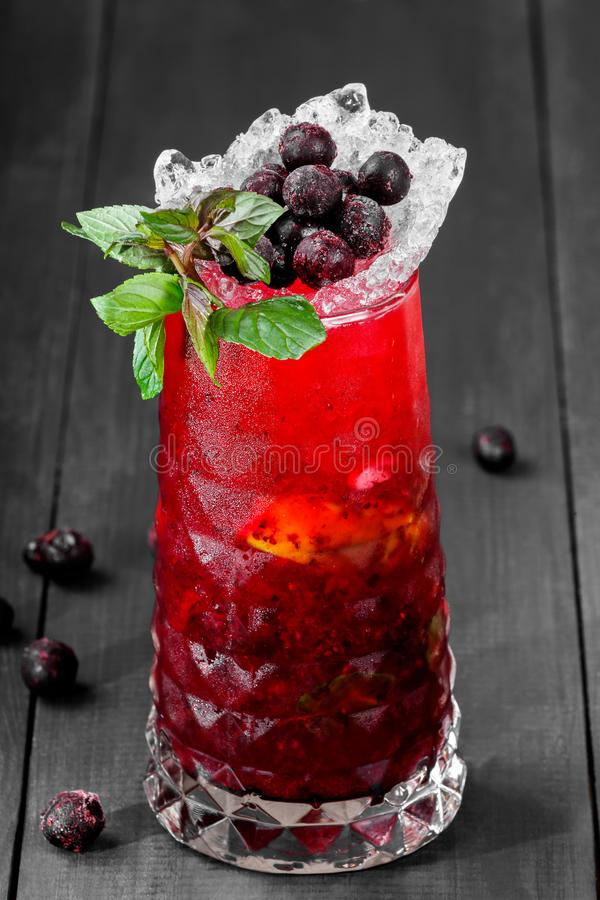Fresh red lemonade with mint, black currant, lime and ice in glass on dark background. Summer drinks and cocktails stock image