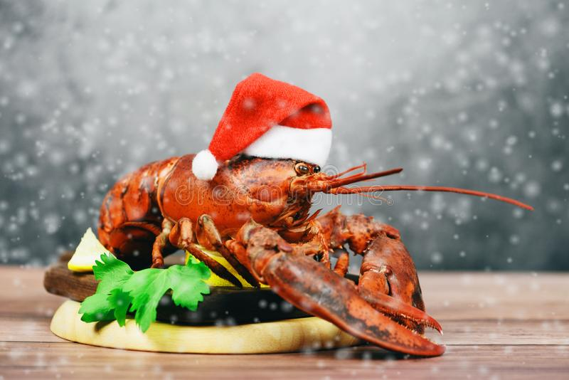 Fresh red lobster with christmas hat shellfish cooked in the seafood restaurant - Steamed lobster dinner food on wooden christmas. Fresh red lobster with stock image