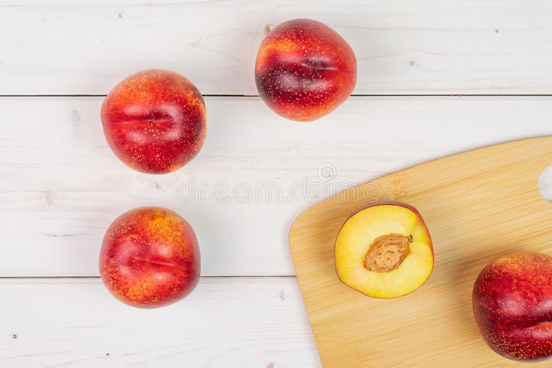 Fresh red nectarine on grey wood. Group of four whole one half of fresh red nectarine on a bamboo cutting board flatlay on white wood stock images