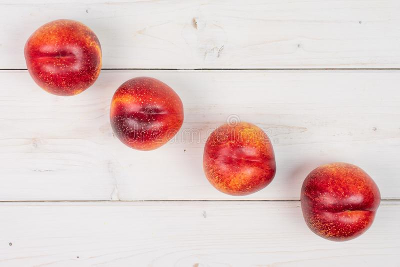 Fresh red nectarine on grey wood. Group of four whole fresh red nectarine placed diagonally in a line flatlay on white wood stock image