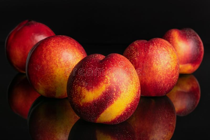 Fresh red nectarine isolated on black glass. Group of five whole fresh red nectarine one is in the front and the rest is layered diagonally isolated on black stock image