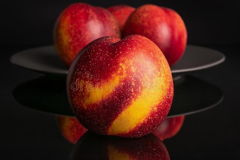 Fresh red nectarine isolated on black glass. Group of four whole fresh red nectarine on a gray ceramic plate isolated on black glass stock image