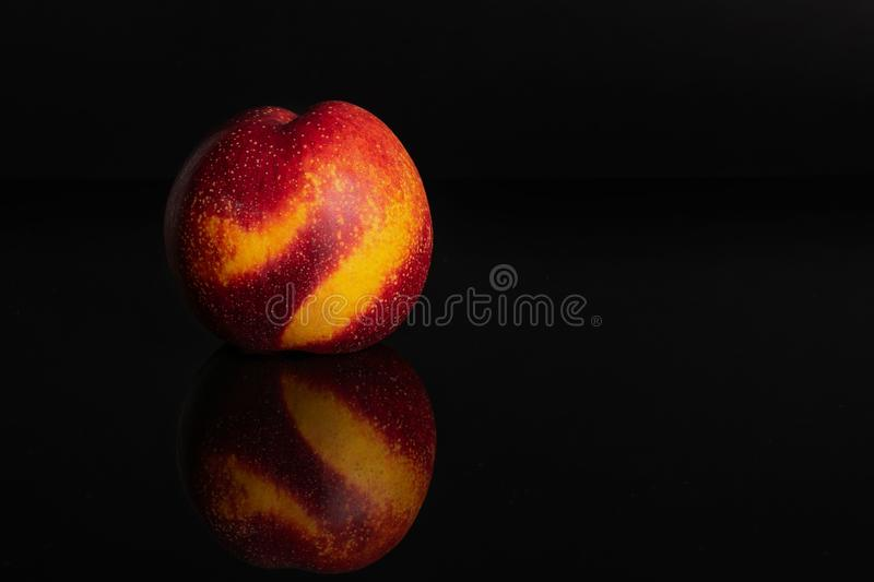 Fresh red nectarine isolated on black glass. One whole fresh red nectarine isolated on black glass royalty free stock photos