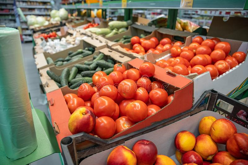 Fresh red organic tomatoes and other vegetables in farmers market or supermarket shelf, healthy food royalty free stock photo