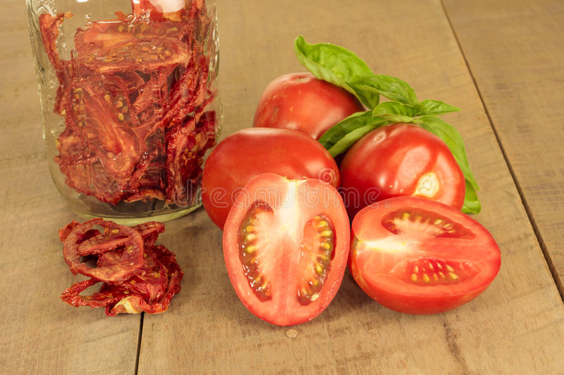 Fresh red paste tomatoes with basil and jar faded stock image