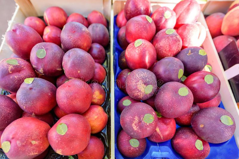 Fresh red peaches with sticker in wooden boxes for sale in local stock image