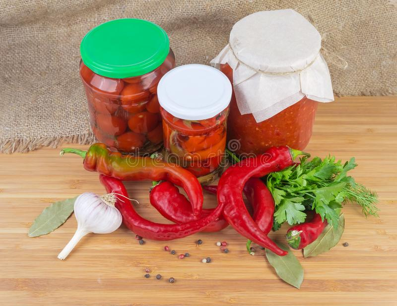 Fresh red peppers chili, pickled chili and other canned vegetables stock photo