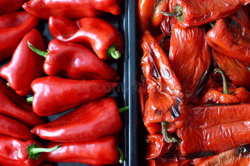 Fresh red peppers and roasted red peppers royalty free stock photo