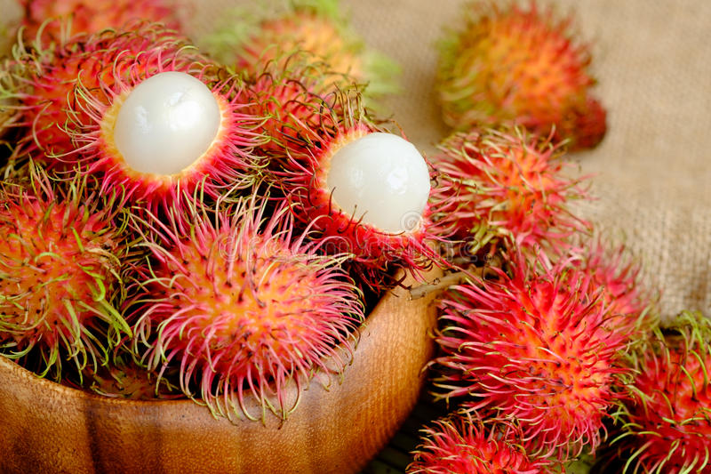 Fresh red rambutan fruit. Red rambutan fruit in wooden bowl royalty free stock images