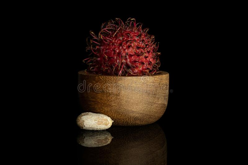 Fresh red rambutan isolated on black glass. Group of one whole one piece of fresh red rambutan in wooden bowl isolated on black glass royalty free stock images