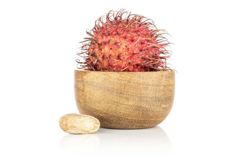 Fresh red rambutan isolated on white. Group of one whole one piece of unpeeled fresh red rambutan in wooden bowl isolated on white background royalty free stock photography