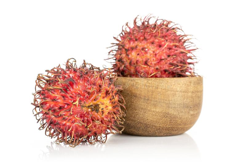 Fresh red rambutan isolated on white. Group of two whole unpeeled fresh red rambutan in wooden bowl isolated on white background royalty free stock photography