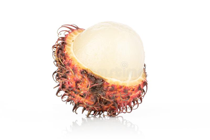 Fresh red rambutan isolated on white. One half of open fresh red rambutan isolated on white background royalty free stock images
