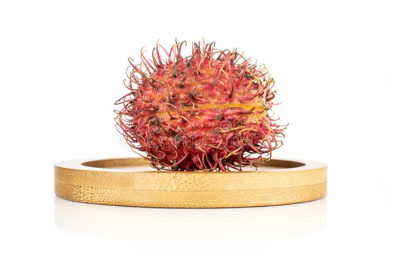 Fresh red rambutan isolated on white. One whole fresh red rambutan on bamboo plate isolated on white background royalty free stock photography