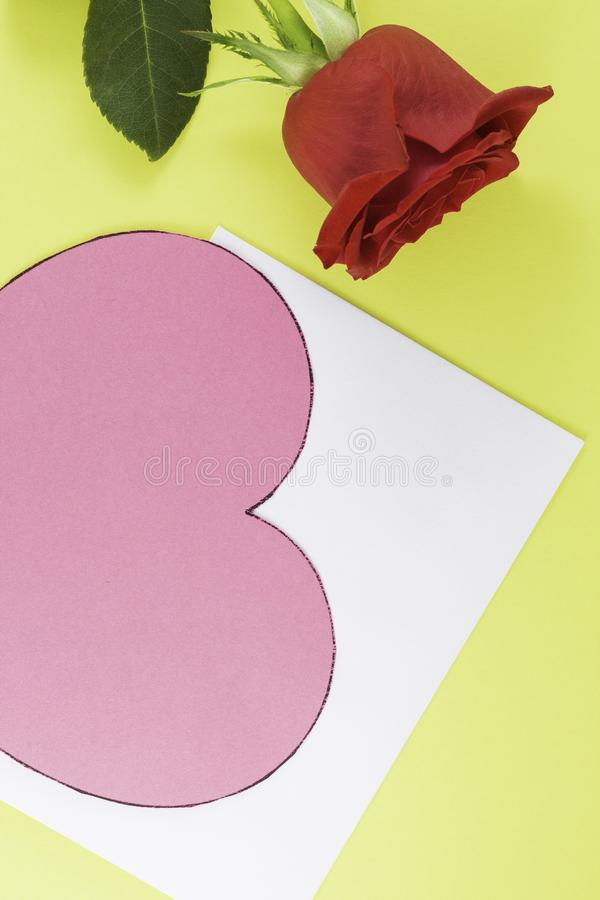 A fresh red rose big bud and petals with green leaves near white empty letter and big pink heart Yellow background royalty free stock photo