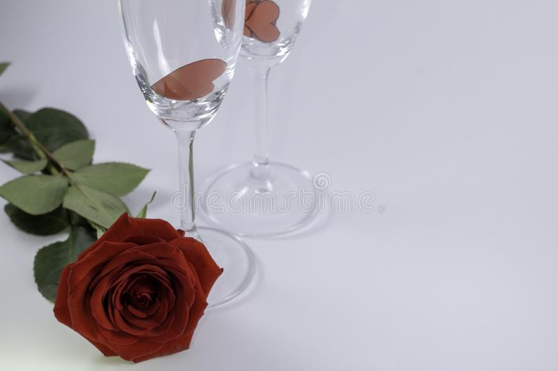 A fresh red rose big bud and petals with green leaves on white background and two champagne glasses and small valentines into them royalty free stock photo