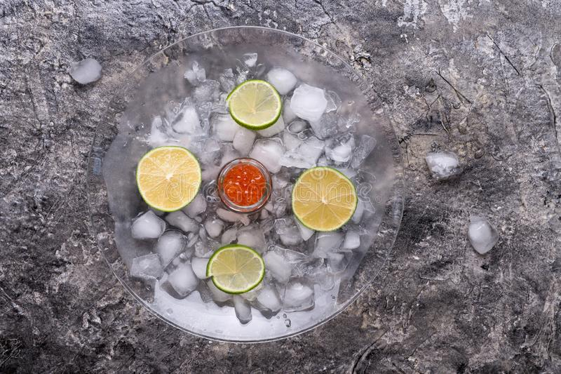 Fresh red  salmon caviar with lime slices around ice. Protein luxury delicacy  healthy food royalty free stock images